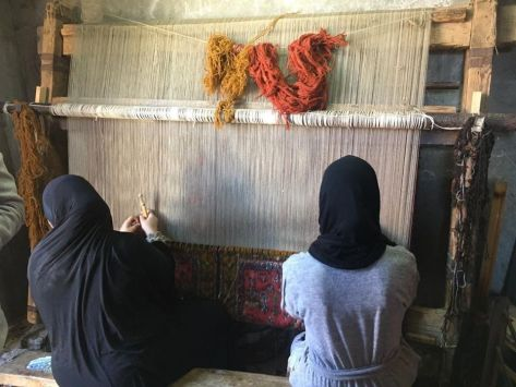 Women of Desya Village making handmade carpets using locally made looms.